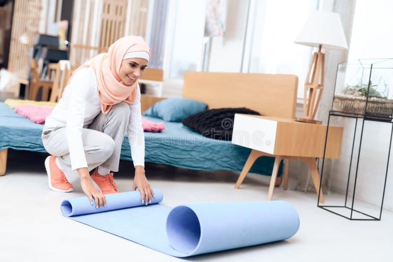 Arabische vrouw die een mat voorbereiden om gymnastiek in de slaapkamer te doen stock afbeeldingen