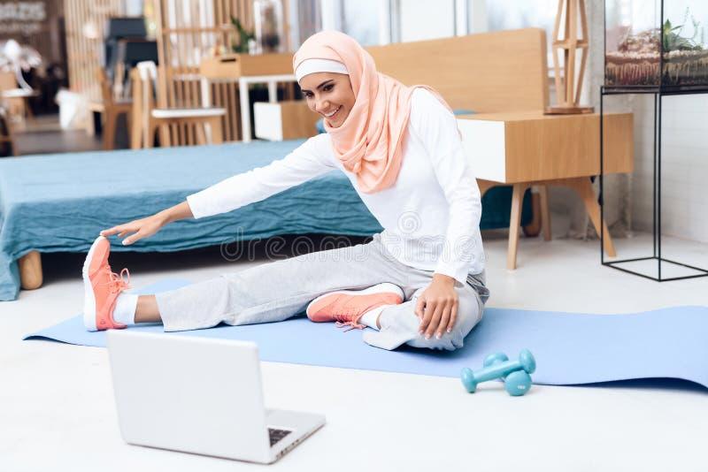 Arabische vrouw die gymnastiek in de slaapkamer doen royalty-vrije stock afbeelding