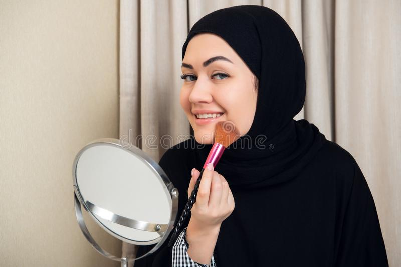 Arabische vrouw die make-up op haar gezicht toepassen, die traditionele Arabische kleding dragen stock foto's