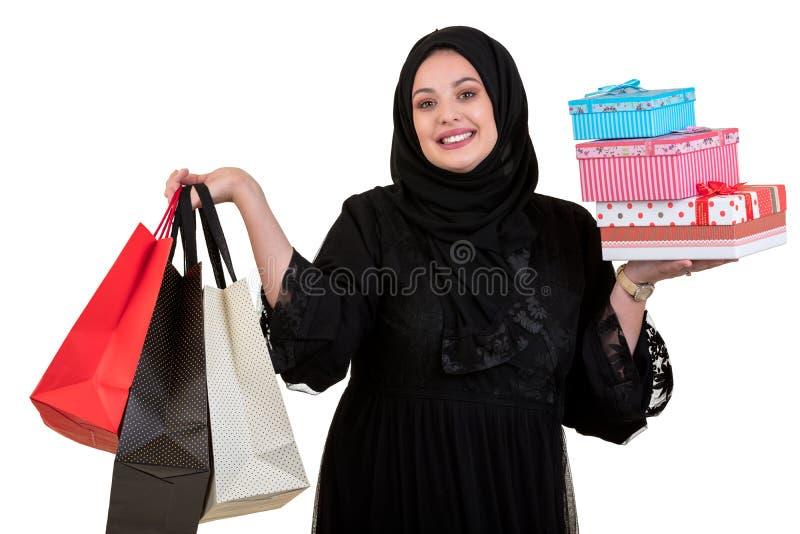 Arabische vrouw dragende die het winkelen zakken en giftdozen op wit worden geïsoleerd royalty-vrije stock afbeeldingen