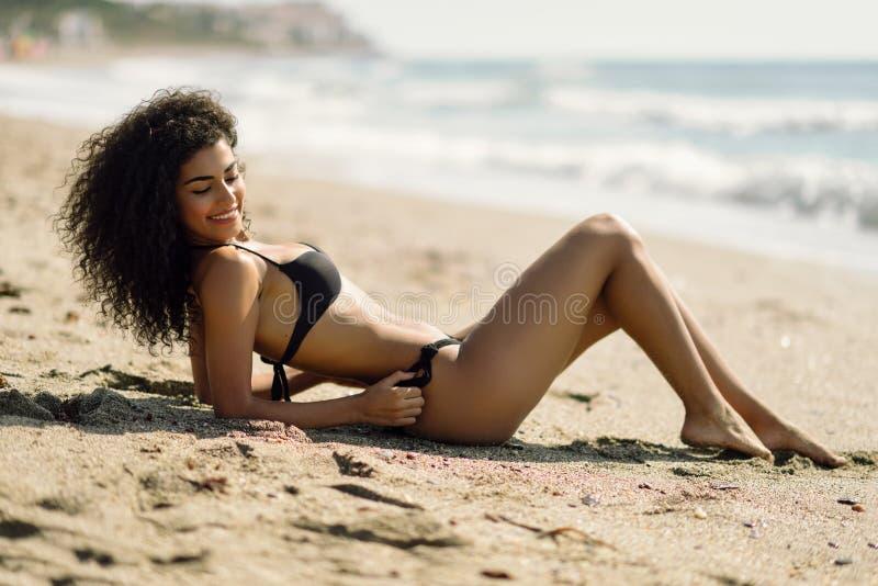 Arabische vrouw met mooi lichaam in bikini die op het strandzand liggen royalty-vrije stock fotografie