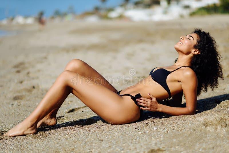 Arabische vrouw met mooi lichaam in bikini die op het strandzand liggen royalty-vrije stock foto's