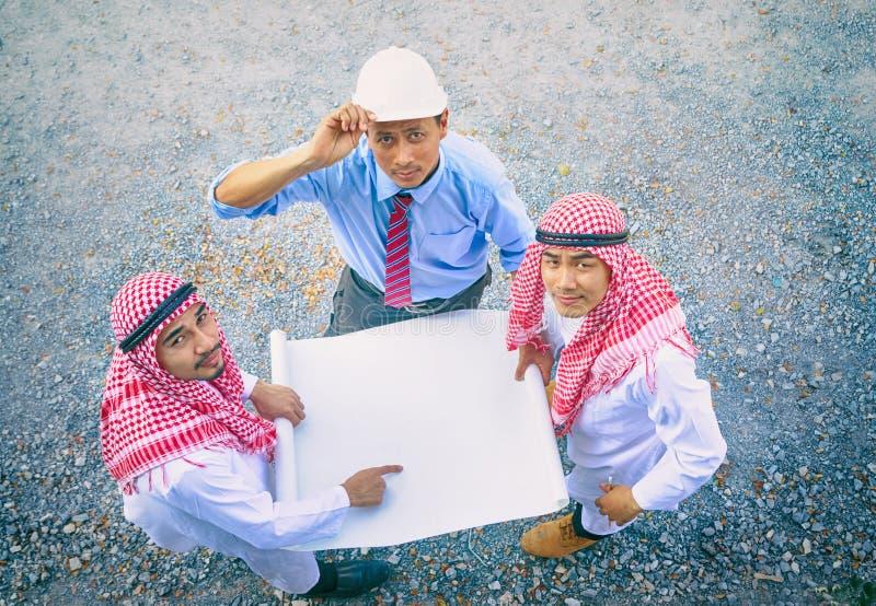 Arabische zakenman en ingenieurs die papar en abou bespreken houden stock fotografie