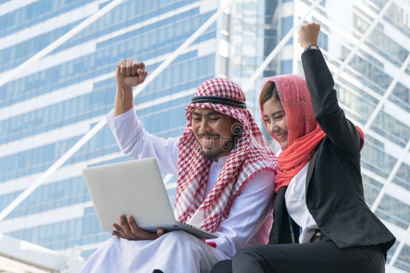 Arabische Zakenman en Onderneemster die computer met behulp van stock afbeeldingen