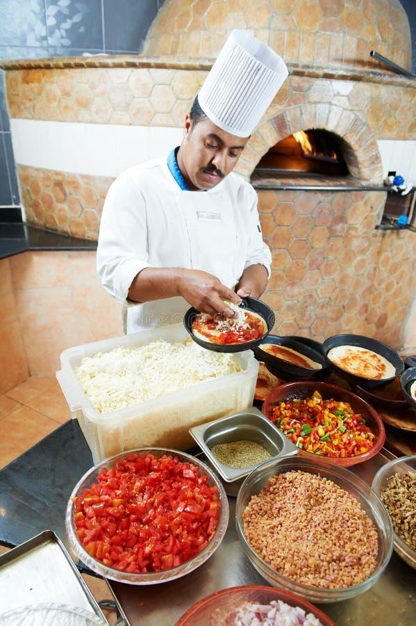 Arabischer Bäckerchef, der Pizza bildet stockbilder
