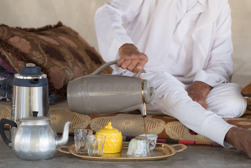 Arabischer beduinischer Mann sitzt auf dem Boden und gießt Tee oder Kaffee von lizenzfreie stockfotografie