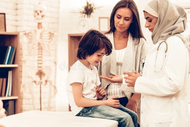 Arabischer Doktor Give Medicine zu kranker Jungen-Lügenbett lizenzfreie stockfotos