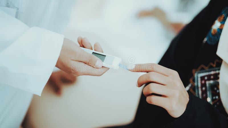 Arabischer Doktor Measuring Blood Sugar Level Woman stockbilder