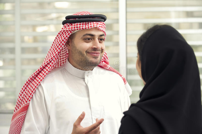 Arabischer Geschäftsmann, der eine Diskussion mit einer arabischen Geschäftsfrau im Büro hat lizenzfreies stockfoto