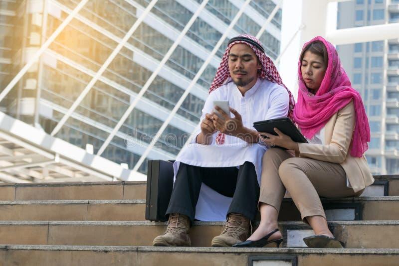 Arabischer Geschäftsmann und Geschäftsfrau, die Kommunikation technolog verwendet stockfoto