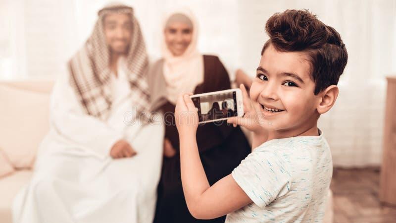 Arabischer Junge, der zu Hause Foto der glücklichen Familie macht stockbild