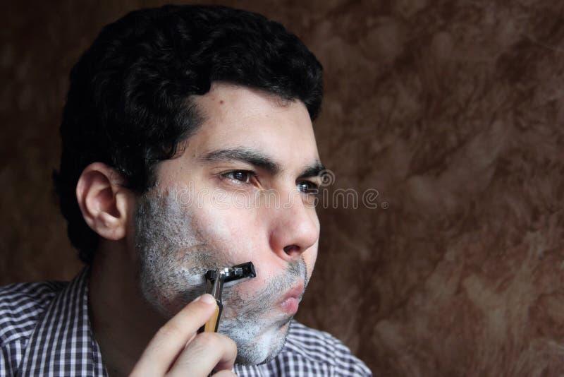 Arabischer junger Geschäftsmann, der seinen Bart mit einem Rasiermesser rasiert lizenzfreie stockfotografie