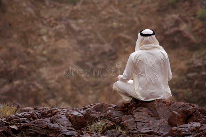 Arabischer Mann, der auf Felsen sitzt lizenzfreies stockfoto