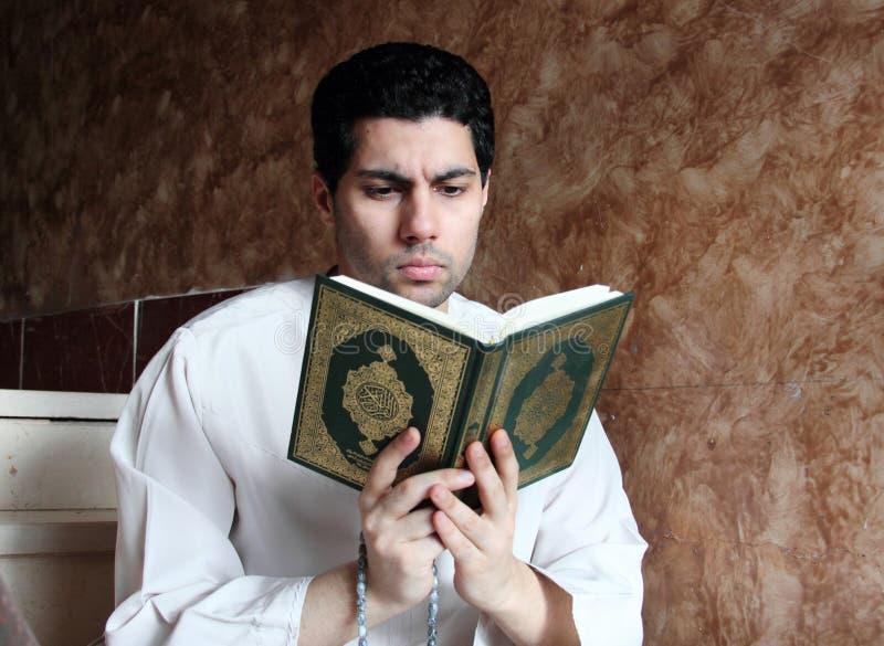 Arabischer moslemischer Mann mit koran Heiliger Schrift mit Rosenbeet stockfotografie