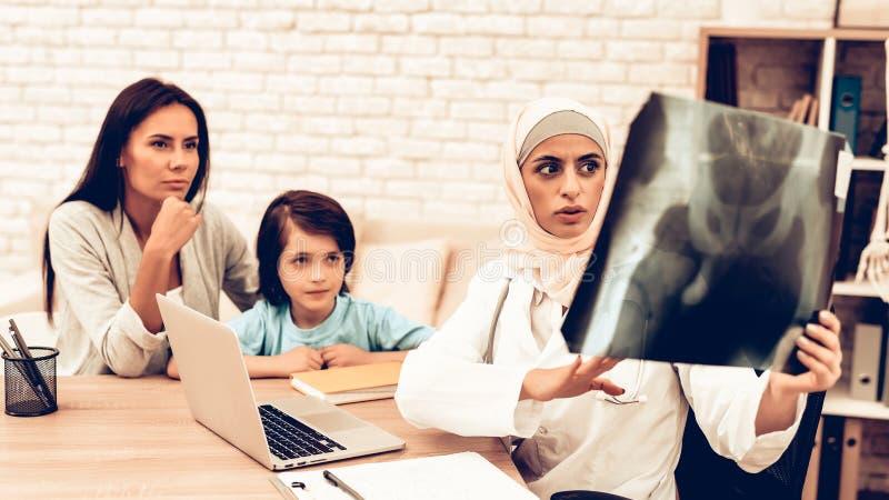 Arabischer Röntgenfilm Doktor-Appointment Holding Kinderarzt Appointment Mom mit krankem Sohn Überzeugte moslemische Ärztin Weari stockfotos