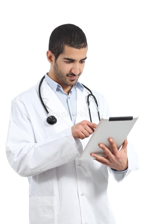 Arabischer saudischer Doktormann, der einen Tablettenleser liest lizenzfreie stockfotografie