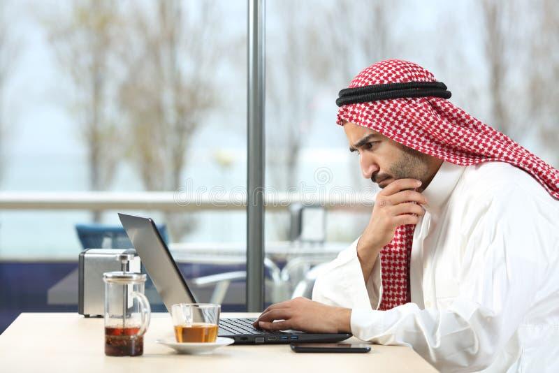 Arabischer saudischer Mann gesorgt mit Laptop stockbilder