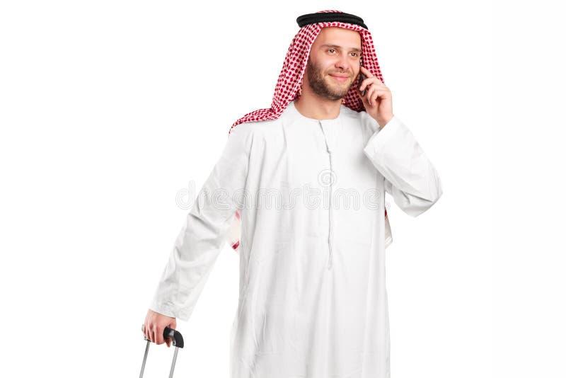 Arabischer Scheich, der am Telefon spricht und ein Gepäck trägt stockfotos