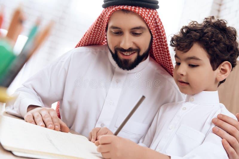 Arabischer Vater unterrichtet kleinen Sohn der Rechtschreibung von Buchstaben stockbild