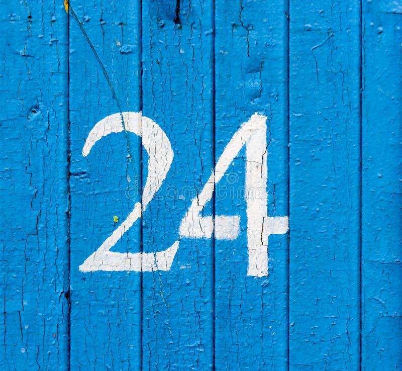 Arabisches Abbildung 24 zwanzig vier gemalt mit Weiß auf einer alten hölzernen Wand bedeckt mit blauer Farbe stockfoto