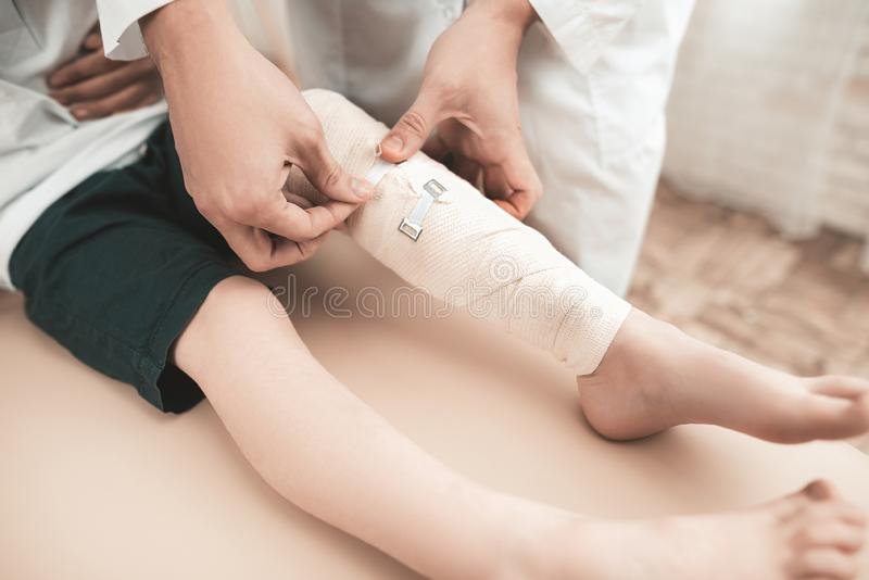 Arabisches Kind-` s Doktor-Is Bandaging Little Bein lizenzfreie stockfotos