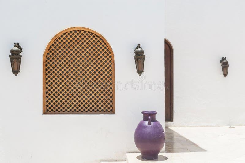 Arabisches weißes Gebäude mit hölzernen Lampen und Krug lizenzfreie stockfotografie