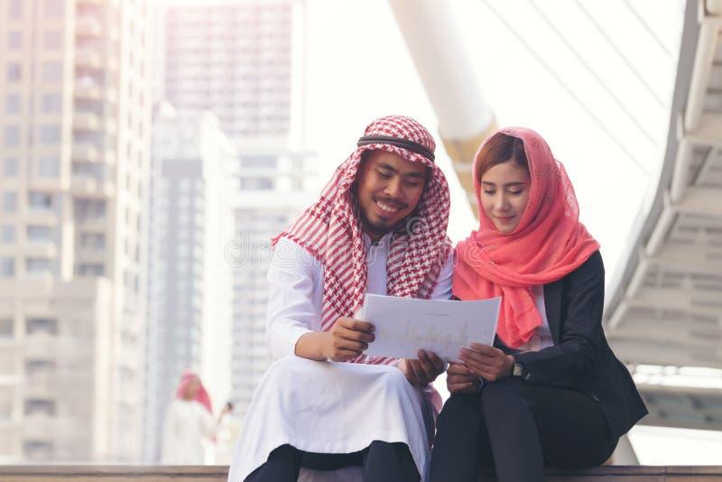 Arabisk arabisk affärsman och arabisk arabisk affärskvinna som tillsammans arbetar arkivbild