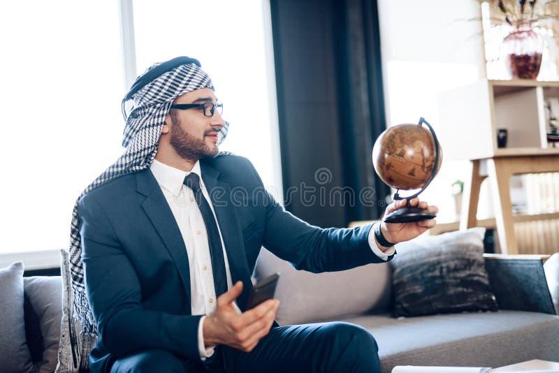 Arabisk affärsman som ser jordklotet på soffan på hotellrum royaltyfri foto