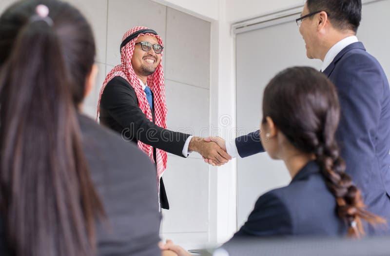Arabisk affärsman som skakar handen över ett avtal till lyckad och lycklig partnerskapfolket det partner som, upp avslutar möte royaltyfri fotografi