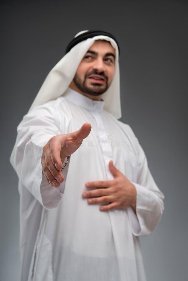 Arabisk affärsman som ut sträcker hans hand royaltyfri bild