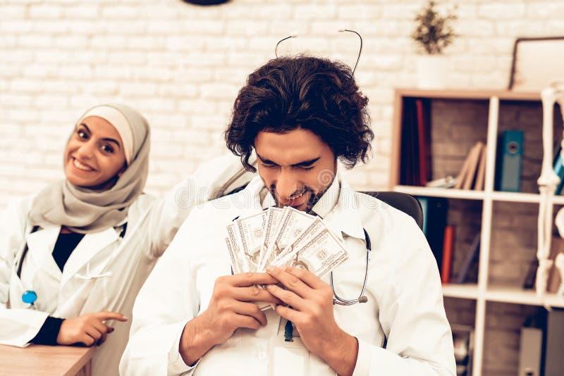 Arabisk doktor Received en lön, avlöningsdagbegrepp royaltyfri fotografi