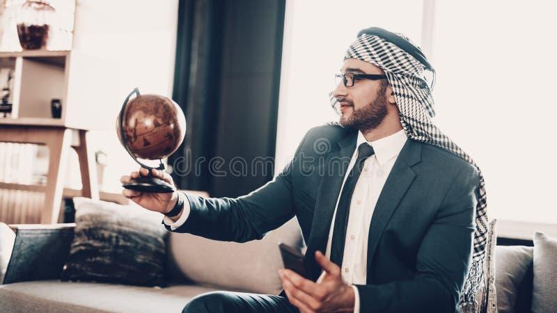 Arabisk hållande telefon och se jordklotet royaltyfri fotografi