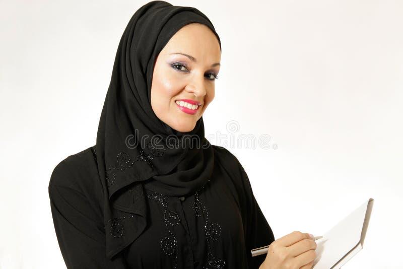 Arabisk kvinna, traditionellt klätt som skriver fotografering för bildbyråer