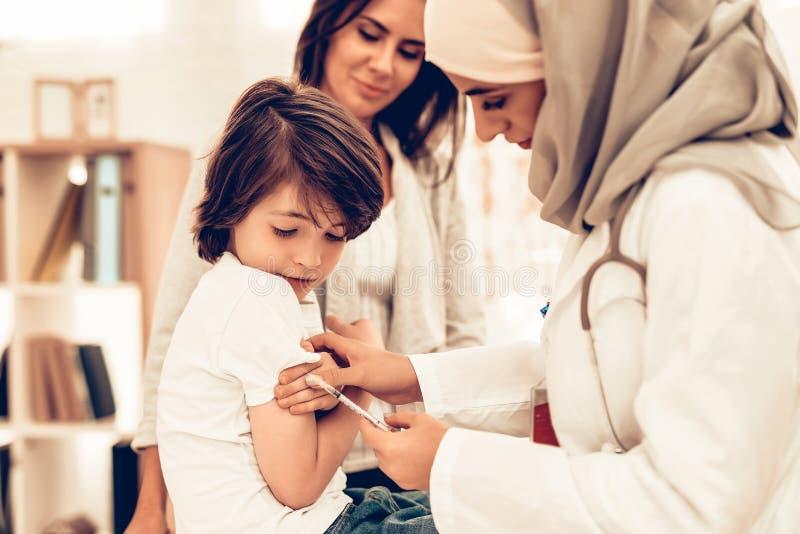 Arabisk kvinnlig doktor Hold Syringe med injektionen arkivbilder