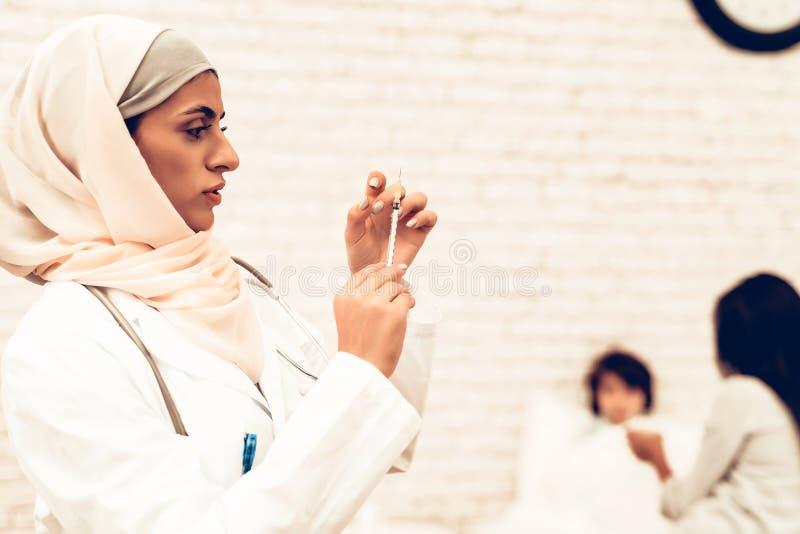 Arabisk kvinnlig doktor Hold Syringe med injektionen royaltyfri bild