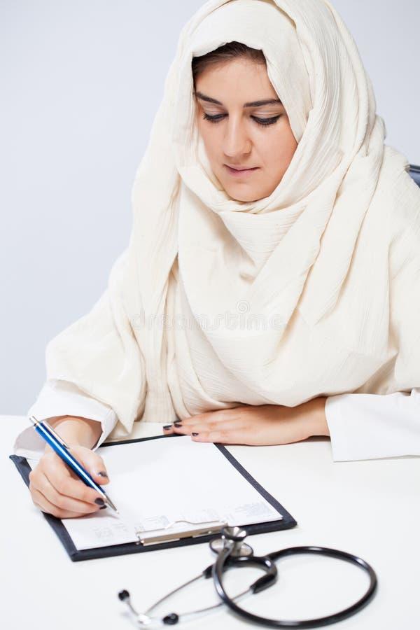 Arabisk kvinnlig doktor under att arbeta arkivbilder