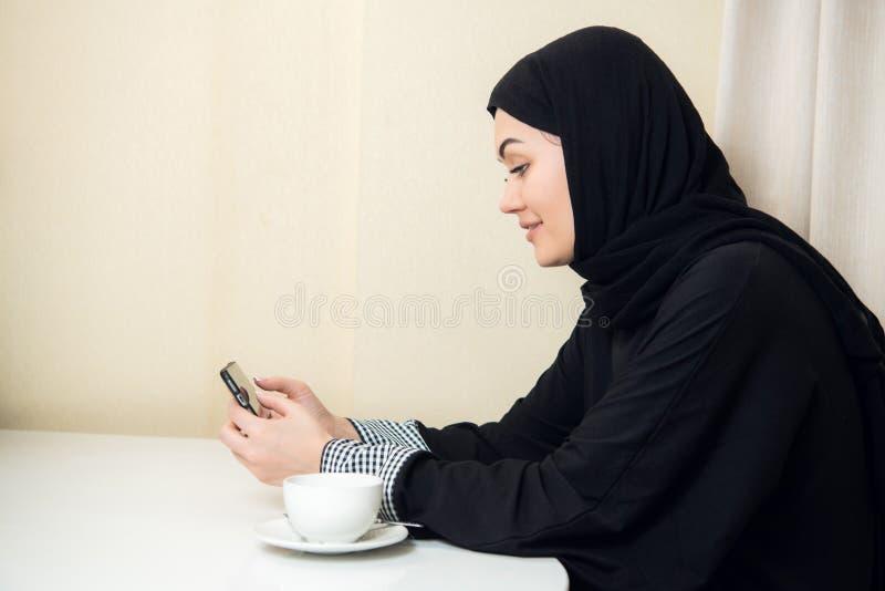 Arabisk lycklig tillfällig kvinna som hemma använder en smart telefon royaltyfria bilder
