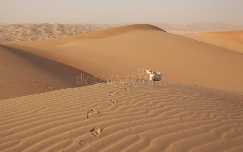 Arabisk man i kandouraen som sitter över en dyn och spelar med sand arkivfoto