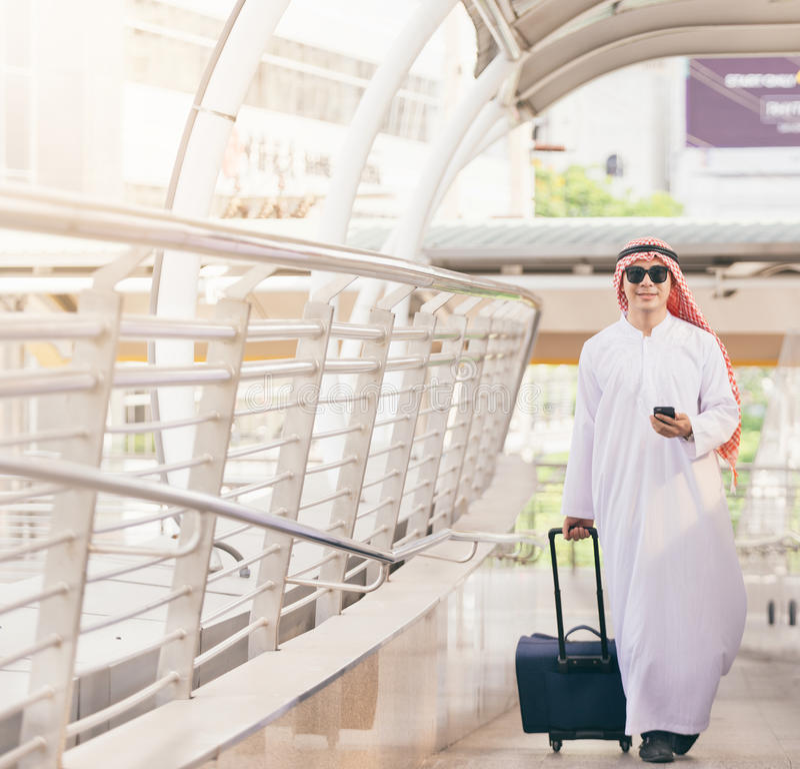 Arabisk man i loppbegrepp Arabisk man för ung saudier i traditionell kläder som går med resväskan på flygplatsbakgrund arkivbilder