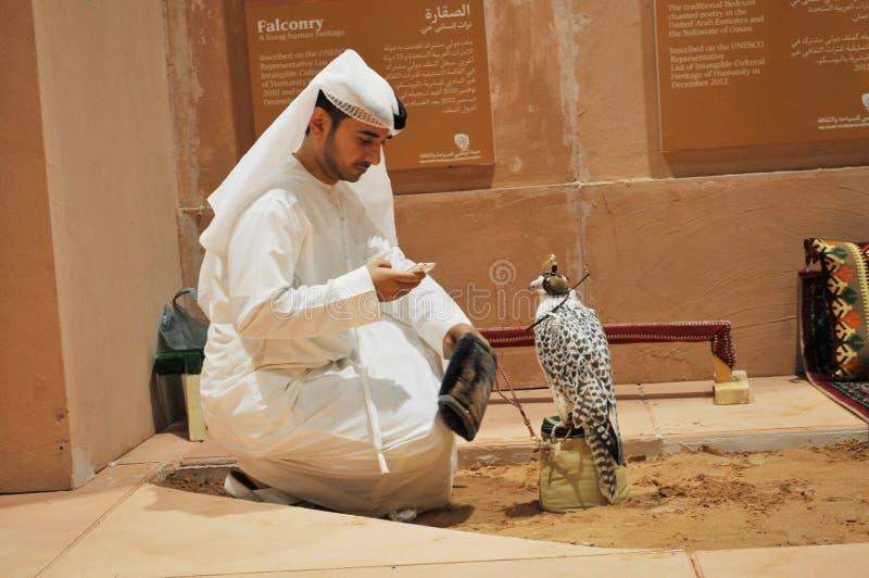 Arabisk man med falken i den Abu Dhabi International Hunting och ryttareutställningen (ADIHEX) arkivfoton