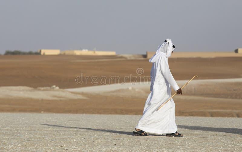Arabisk man som går i en öken royaltyfria bilder