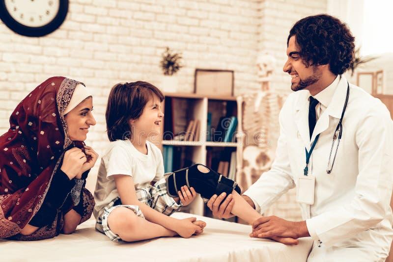 Arabisk manlig doktor Bandaging Leg Injury av barnet arkivbilder