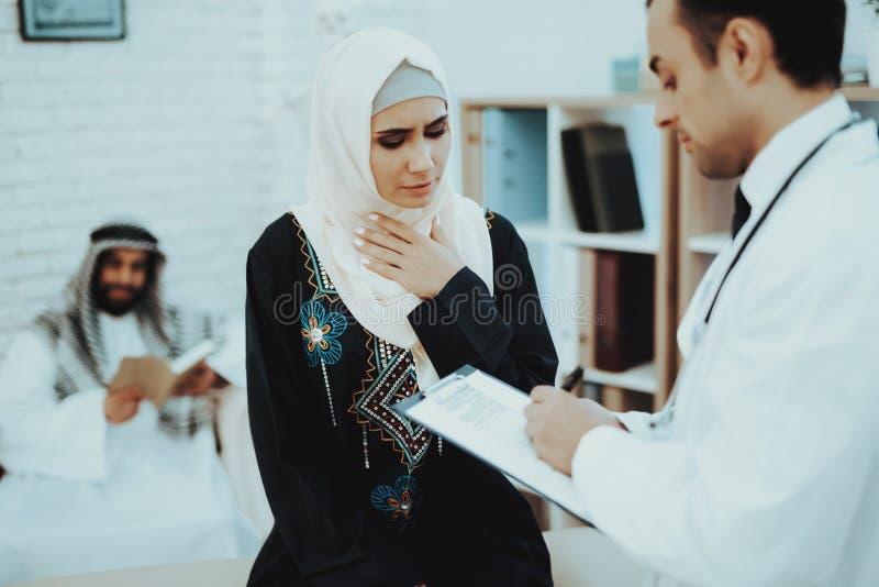 Arabisk manlig doktor Examining en muslimsk kvinna arkivbilder