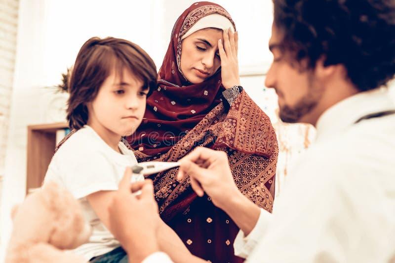Arabisk manlig doktor Examining Measuring Temperature arkivbilder
