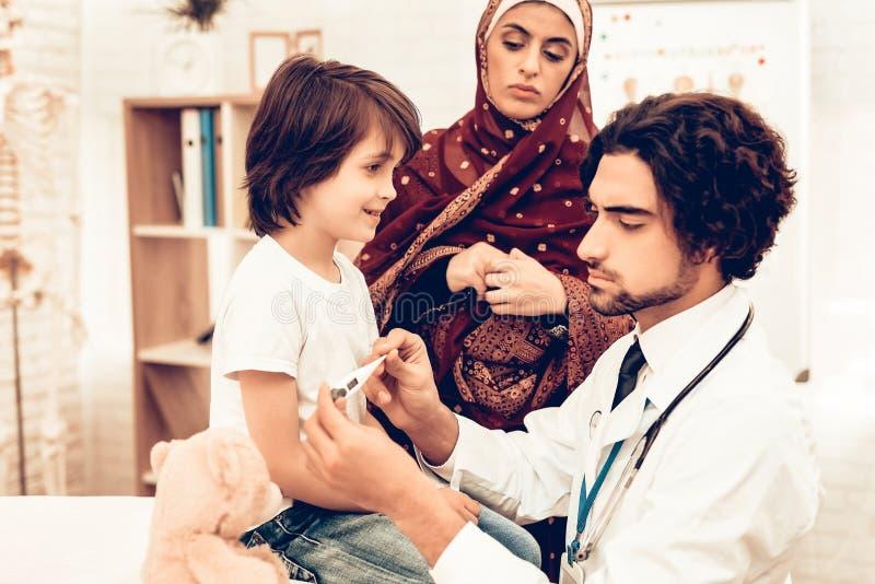 Arabisk manlig doktor Examining Measuring Temperature royaltyfri foto