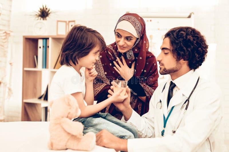 Arabisk manlig doktor Give Medicine till den sjuka pojken Säker muslimsk manlig doktor Giving Glass av medicin Barn på det pediat royaltyfria bilder