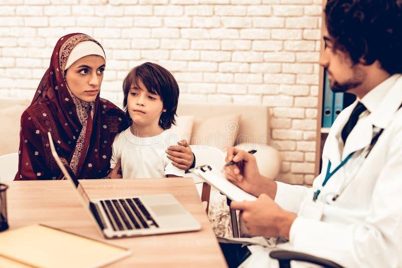 Arabisk moder med sonen på doktors Tidsbeställning arkivbilder