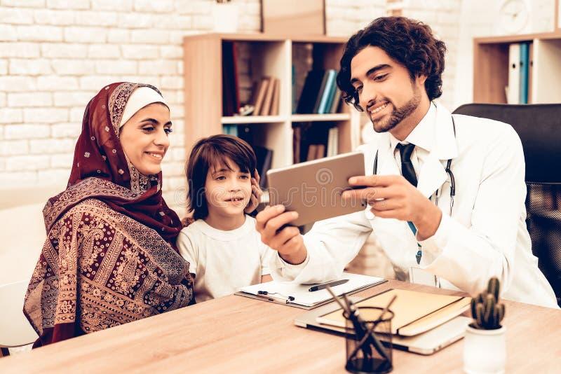 Arabisk moder med sonen på doktors Tidsbeställning arkivbild