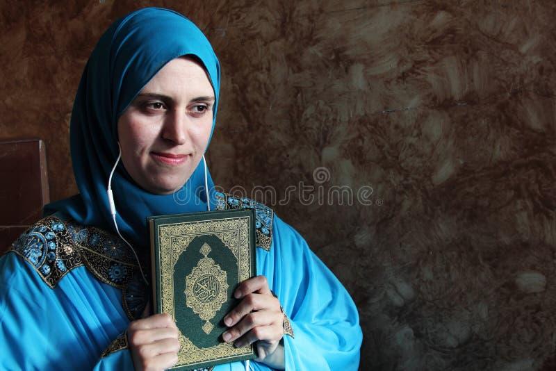 Arabisk muslimkvinna med boken och hörlurar med mikrofon för Koranen den islamiska heliga royaltyfri foto