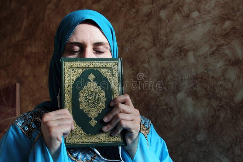 Arabisk muslimkvinna med boken och hörlurar med mikrofon för Koranen den islamiska heliga royaltyfri fotografi